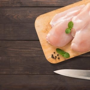 Top view of a raw chicken on top of a cutting board and knife on wooden table background.